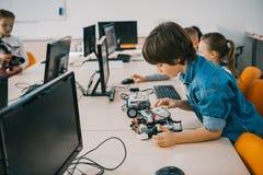 修建机器人的被集中的青少年的孩子在类词根 图库摄影