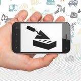 修建概念:递拿着有砖墙的智能手机在显示 免版税图库摄影
