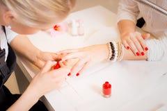 修指甲专家绘画红色客户的钉子 库存图片