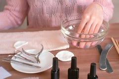 修指甲在家 浸洗她的在一个碗的妇女手水 递特写镜头,在桌上的修指甲工具 库存照片