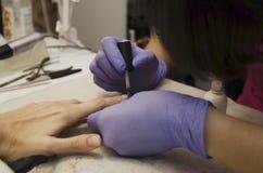 修指甲大师用一种特别钉子定形剂盖客户的钉子 免版税库存图片