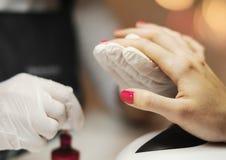 修指甲大师绘与指甲油的钉子在美容院 免版税库存照片
