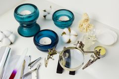 修指甲工具、蜡烛在绿松石烛台,棉花和陶瓷玩偶,异常的放大镜 免版税库存照片