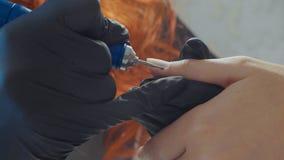 修指甲师应用电指甲锉钻子于在女性手指的修指甲 图库摄影