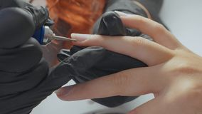 修指甲师应用电指甲锉钻子于在女性手指的修指甲 免版税库存照片