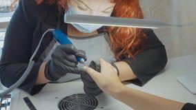 修指甲师应用电指甲锉钻子于在女性手指的修指甲 免版税库存图片