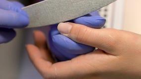 修指甲师特写镜头宏指令取消老指甲油与客户 钉子orocessing的锯切 手工修指甲过程 股票视频