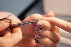 修指甲的培训班的一名学生一个夫人客户的手有修指甲剪刀的为表皮做准备 库存照片
