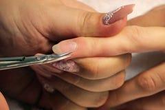 修指甲的培训班的一名学生一个夫人客户的手有修指甲剪刀的为表皮做准备 免版税库存照片