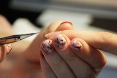 修指甲的培训班的一名学生一个夫人客户的手有修指甲剪刀的为表皮做准备 图库摄影