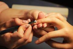 修指甲的培训班的一名学生准备一个夫人客户的手有工具的为以前刮刮板 免版税库存照片