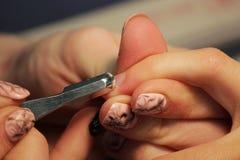 修指甲的培训班的一名学生准备一个夫人客户的手有工具的为以前刮刮板 免版税库存图片