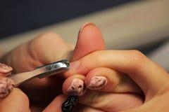 修指甲的培训班的一名学生准备一个夫人客户的手有工具的为以前刮刮板 库存照片