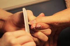 修指甲的培训班的一名学生在应用紫胶前准备一个夫人客户的手有文件的 免版税图库摄影