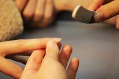 修指甲的培训班的一名学生在应用紫胶前准备一个夫人客户的手有文件的 库存图片