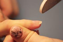 修指甲的培训班的一名学生在应用紫胶前准备一个夫人客户的手有文件的 免版税库存照片