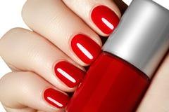 修指甲 有红色指甲油的美丽的被修剪的妇女的手 免版税库存图片