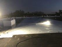 修改过的盖帽板料商业屋顶平台转换撤除的夜间视图向与安全旗子的TPO 图库摄影