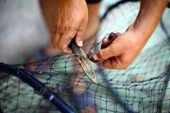 修理一个捕鱼网 免版税库存照片