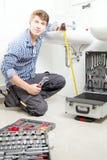 修理一个水槽的男性水管工画象在卫生间里 图库摄影