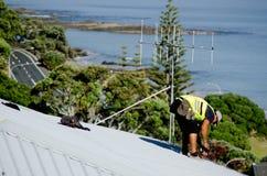 修理一个漏的屋顶的盖屋顶的人 免版税库存图片