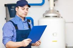 修理一个热水加热器的技术人员 库存图片