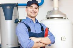 修理一个热水加热器的水管工 免版税库存照片