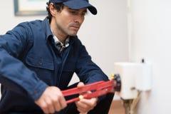 修理一个热水加热器的水管工 库存照片
