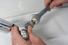 修理一个龙头在卫生间里 免版税图库摄影