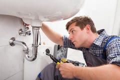 修理一个水槽的年轻水管工在卫生间里 免版税图库摄影