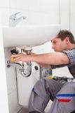修理一个水槽的年轻水管工在卫生间里 免版税库存照片