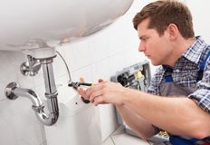修理一个水槽的年轻水管工在卫生间里 库存图片