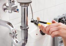 修理一个水槽的年轻水管工在卫生间里 库存照片