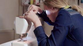 修理一台缝纫机的年轻裁缝 螺纹被缠结并且被困住 股票录像