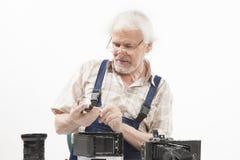 修理一台老照相机的人 免版税图库摄影