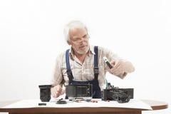 修理一台老照相机的人 图库摄影