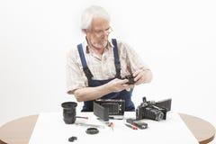 修理一台老照相机的人 免版税库存图片