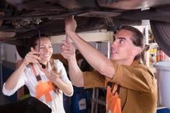 修理一辆残破的汽车的机械工 免版税库存照片