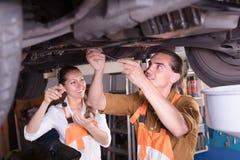 修理一辆残破的汽车的机械工 图库摄影