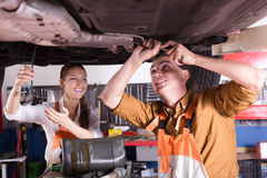 修理一辆残破的汽车的机械工 库存图片