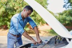 修理一辆残破的汽车的被注重的人 免版税库存照片