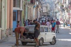修理一辆汽车的人在哈瓦那,古巴 免版税库存照片