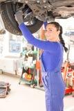 工作在水力舷梯的汽车的女性技工 库存照片