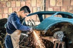年轻修理一辆老葡萄酒汽车的人机械工作者 免版税图库摄影