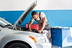修理一辆被举的汽车的技工 库存图片