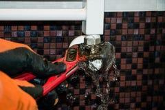 修理与一把板钳的幅射器在卫生间里 免版税图库摄影