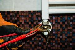 修理与一把板钳的幅射器在卫生间里 库存照片