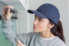 修理与螺丝刀的妇女窗帘在办公室 库存图片