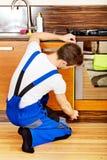 年轻修理人测量的厨柜 免版税库存图片