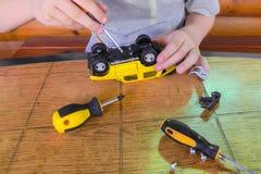 修理儿童黄色打字机男孩手拿着一把螺丝刀 图库摄影